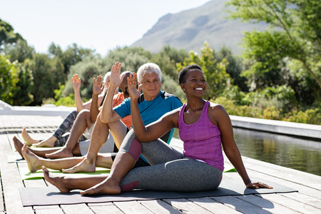 Photo pour Senior men and mature women doing yoga exercise near swimming pool outdoor. Multiethnic people in a row practicing stretching exercise. Group of middle aged sporty people practicing pilates lesson. - image libre de droit