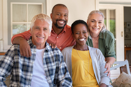 Photo pour Senior couple with mature man and african woman posing for a photo sitting at courtyard. Portrait of happy multiethnic people sitting on couch under patio. Cheerful men and beautiful women looking at camera. - image libre de droit