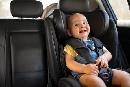 Photo pour Portrait of happy little child sitting in car seat with safety belt, enjoying road trip. Cute baby boy smiling and having fun while being in the infant car seat. Laughing curious toddler enjoying travel, copy space. - image libre de droit