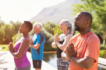 Photo for Four senior people meditating with joined hands and closed eyes breath deeply. Multiethnic group doing breathing exercise during yoga session outdoor. Class of mature people doing meditation with joined hands and relaxing together at park. - Royalty Free Image