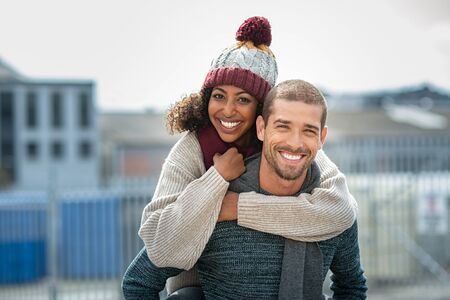 Photo pour Portrait of young man giving piggyback ride to african woman in the city. Happy boyfriend and smiling girlfriend wearing sweater and wool scarf looking at camera. Multiethnic couple having fun in street during winter season. - image libre de droit