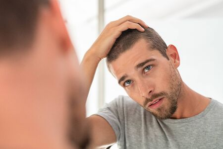 Photo pour Young unshaven man looking at mirror in bathroom at home. Handsome guy looking at his face in mirror, checking hair and hairline. Man in pijamas concerned with hair loss. - image libre de droit