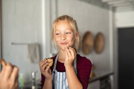 Photo for Cheerful little girl tasting chocolate chip cookies. Girl wearing apron and eating chocolate chip cookie in kitchen with grandmother. Happy girl enjoying self made biscuits at home with funny expression. - Royalty Free Image