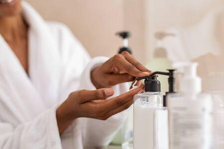 Photo pour African woman hands using cosmetic liquid soap in bathroom. Close up of girl black hands in bath robe using body lotion dispenser after shower. Black girl putting pomade on hand from pump. - image libre de droit