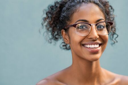 Photo pour Cheerful young woman with naked shoulder wearing eyeglasses and looking at camera. Smiling african american woman with curly hair wearing spectacles isolated against blue background. Portrait of happy black girl with copy space. - image libre de droit