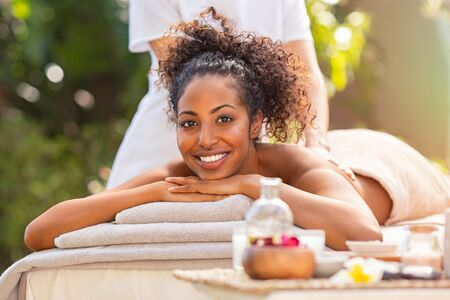 Photo pour Young african woman getting spa massage outdoor in a tropical environment. Happy woman lying on stomach on massage table getting back beauty treatment. Beautiful girl doing massage and spa treatment in natural setting. - image libre de droit