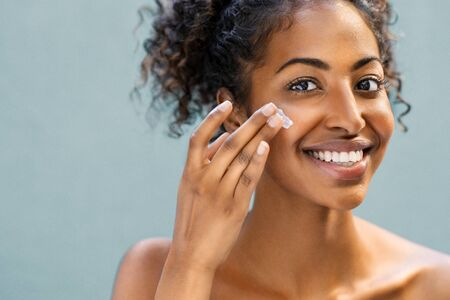Photo pour Beautiful african american woman with smooth skin applying moisturizer face cream to her cheek. Beauty young woman taking care of skin. Happy girl applying cosmetic moisturiser treatment isolated on background and looking at camera with copy space. - image libre de droit