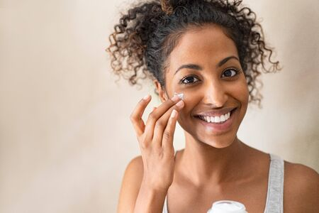 Photo pour Smiling african girl with curly hair applying facial moisturizer while holding jar and looking at camera. Portrait of young black woman applying cream on her face isolated on beige background. Close up of happy attractive beauty woman caring of her skin standing on light brown wall with copy space. - image libre de droit