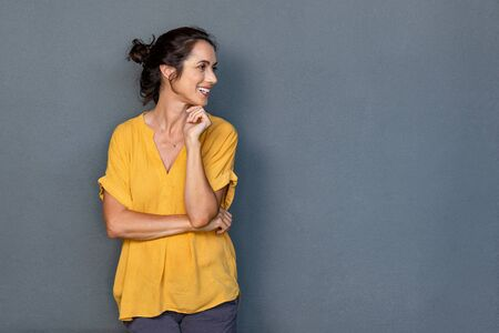 Foto de Mature beautiful latin woman isolated on grey background looking on side with copy space. Portrait of positive brunette woman smiling and looking away. Happy middle aged lady standing against grey wall and thinking. - Imagen libre de derechos