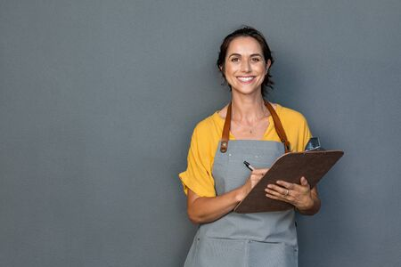 Foto de Happy smiling waitress taking orders isolated on grey wall. Mature woman wearing apron while writing on clipboard standing against gray background with copy space. Cheerful owner ready to take customer order while looking at camera. Small business concept. - Imagen libre de derechos