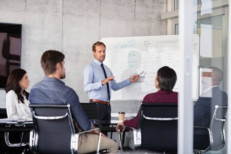 Foto de Mature businessman giving presentation to his colleagues in modern office. Formal leader presenting new project to business partners in conference room using white board. Businessman in a meeting showing business progressions in boardroom. - Imagen libre de derechos