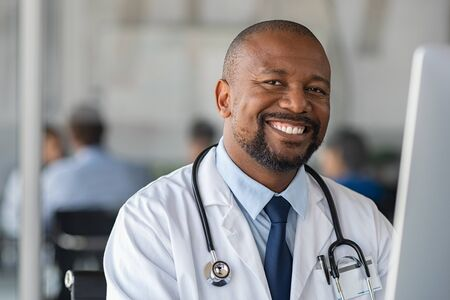 Photo pour Happy smiling african doctor looking at camera in medical office. Portrait of black man doctor working on laptop in modern hospital. Confident and reliable mature nurse using computer to analyze medical report of patient. - image libre de droit