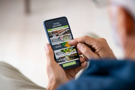 Photo for Top view of man hands holding smartphone while order food delivery at home. Back view of mature man using food delivery app with mobile phone to order lunch. - Royalty Free Image
