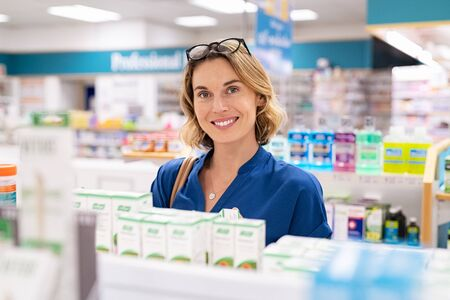 Photo pour Portrait of smiling woman choosing dietary supplement at pharmacy in shopping mall. Happy mature woman customer buying lotion in skincare section of chemist's. Woman checking medicine and drugs in shelf at drugstore while looking at camera. - image libre de droit