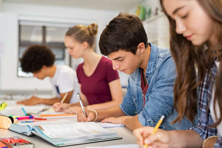 Foto de Group of college students studying in classroom writing notes during lesson. Focused guy and girls studying in college library sitting at desk. Group of multiethnic university students doing research sitting in a row. - Imagen libre de derechos