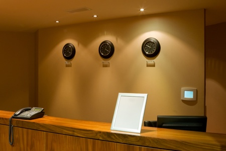 hotel reception desk with phone and row of clock on the wall