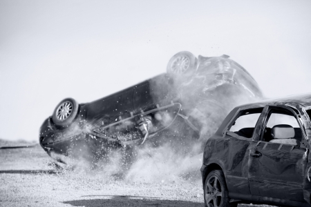 two cars turned upside-down after road collision, monohromatic