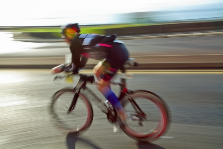 Photo pour Athlete riding bicycle at sunny day on coastal road, blurred motion - image libre de droit