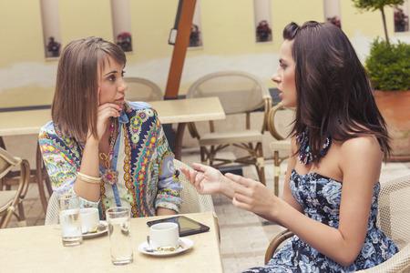 Two girlfriends talking in cafe
