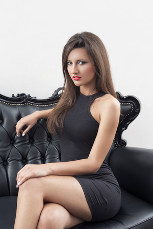 Elegant woman in black dress sitting on black sofa