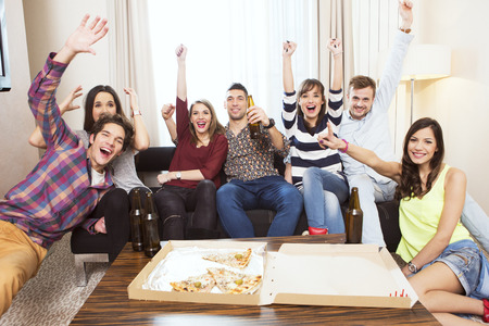 Photo pour Group of friends watching TV match and cheering - image libre de droit