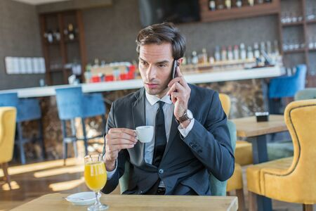 Photo pour Handsome young businessman talking on the cell  phone in hotel cafe - image libre de droit
