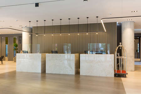 Photo for Interior of a hotel lobby with reception desks with transparent covid plexiglass lexan clear sneeze guards - Royalty Free Image