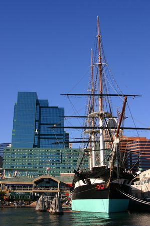 A historic boat docked in Downtown Baltimore Inner Harbor with skyscrapers in background