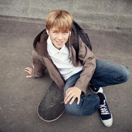 Photo pour School teen sits on skateboard near school, day - image libre de droit