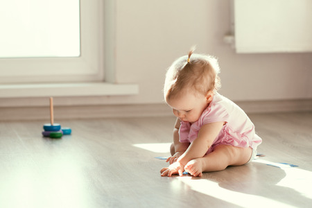 Photo pour Little girl playing with pyramid on floor, kindergarten, precocity - image libre de droit
