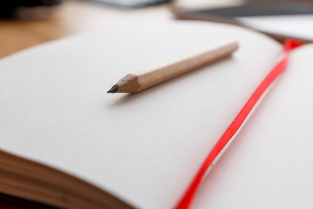 Photo pour Close-up of open notebook and pencil, red book-mark. - image libre de droit