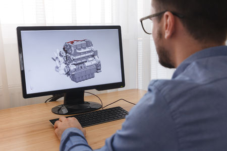 Photo for Engineer, Constructor, Designer in Glasses Working on a Personal Computer. He is Creating, Designinga New 3D Model of Car Engine, Motor in CAD Program. Freelance Work. - Royalty Free Image