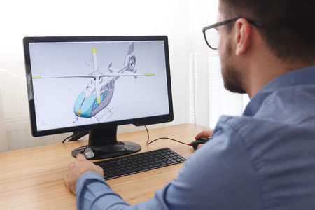 Photo pour Engineer, Constructor, Designer in Glasses Working on a Personal Computer. He is Creating, Designing a New 3D Model of Helicopter in CAD Program. Freelance Work. - image libre de droit