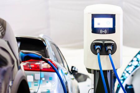 Photo pour Modern electrical fast charger to electrical or hybrid PHEV automobiles. Future energy power. Ecology friendly charger. Clean ecology concept. Home electric car battery charger. - image libre de droit