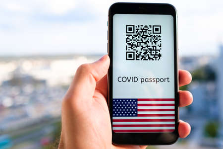 Photo pour Covid passport with QR code with USA flag on the screen in smartphone in mans hand on the background of cityscape, May 2021, San Francisco, USA. - image libre de droit