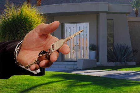Image of a beautiful Desert home in california as real Estate salesman Hands Over Keys
