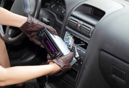 Gloved hands of a thief stealing a car radio from the dashboard of a car with the wiring exposed