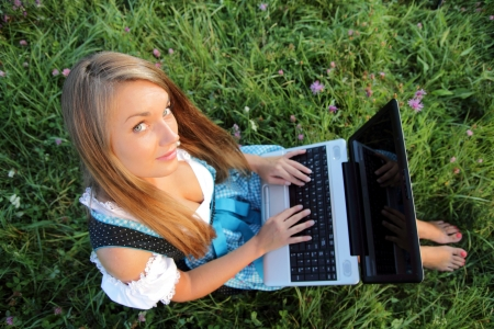 Bavarina Woman in Flowering Meadow with Laptop from aboveの写真素材