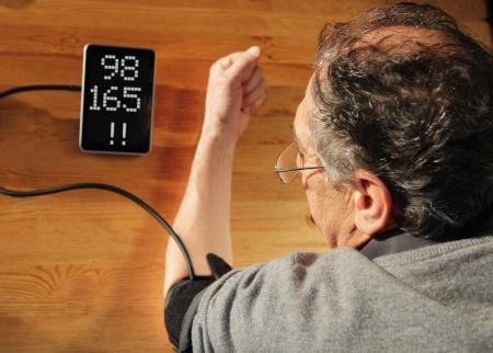 Elder men with hypertension measuring blood pressure
