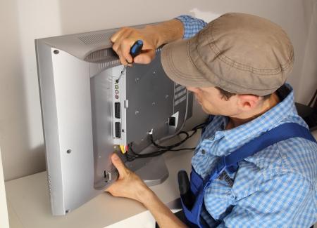 Electrician repairing a TV