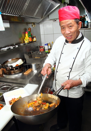 A Asia cook with wok take away