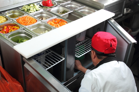 A Asian cook in a citchen working on a vegetable buffet bar