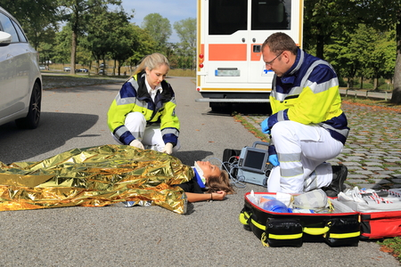Photo pour Two paramedics helping a woman after a traffic accident  - image libre de droit