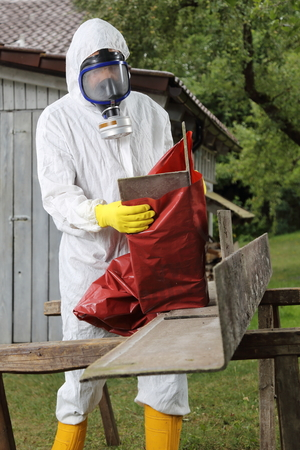 Foto de A Worker with mask packing Asbestos Disposal - Imagen libre de derechos