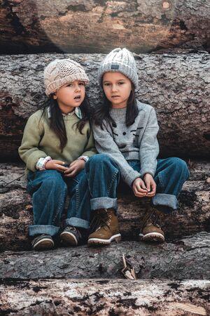 Foto de Little girl whispers a secret to her sistersitting on the logs. - Imagen libre de derechos