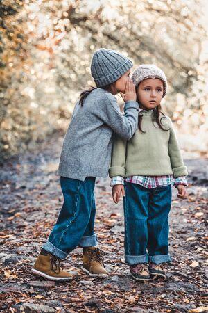 Foto de Little girl whispers a secret to her sistersitting against the background of nature. Sisters friendship - Imagen libre de derechos