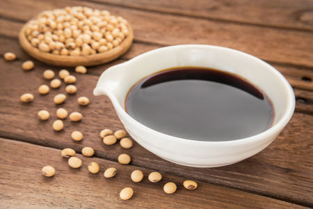 Soy sauce and soy bean on wooden background