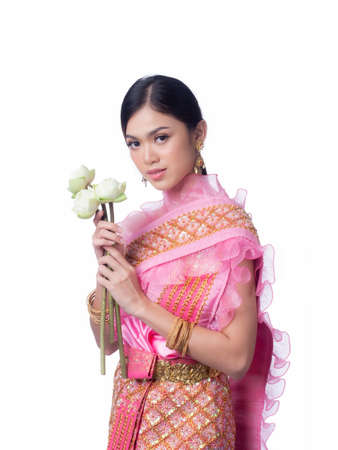Photo pour A charming Thai woman in ancient Thai dress holding a lotus flower that is used for worshiping religious monks for the Loy Krathong Festival in Thailand - image libre de droit
