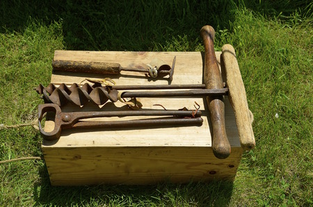 Old hand tools are displayed on an old wooden box