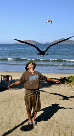 MAZATLAN, MEXICO, January 31, 2017: A identified man entertains and earns a living feeding birds with meat on the end of a stick on the Malecon walkway in Mazatlan